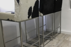 black and white cowhide stools with backs and steel frames.