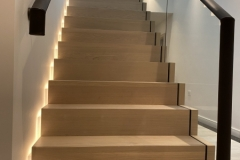 Leather fitted to oval handrails on wall mounted brackets and on glass balustrade