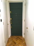 Leather panels applied to interior front door of London apartment.