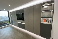Wall to wall units with TV and lighting.