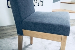 Grey fabric dining chair with stud detail.