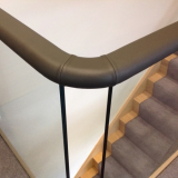 Flat handrail on glass, covered in leather.